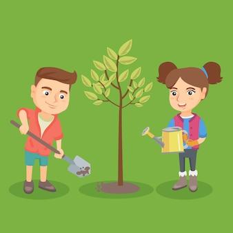 Menino caucasiano pequeno e menina que plantam a árvore.