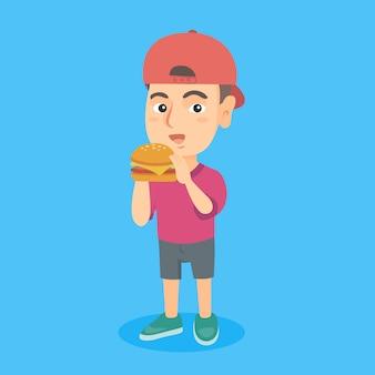 Menino caucasiano pequeno que come um hamburger.
