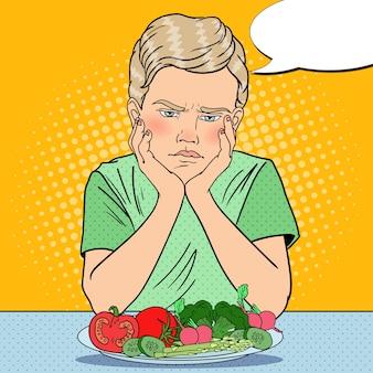 Menino chateado com prato de legumes frescos