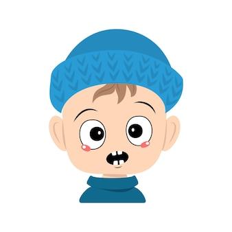 Menino com emoções em pânico surpreso rosto olhos chocados em chapéu de malha azul criança fofa com medo expresso ...