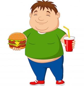Menino com excesso de peso, segurando o hambúrguer e refrigerante