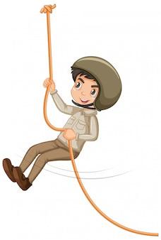 Menino com roupa de safari, corda de escalada no fundo branco