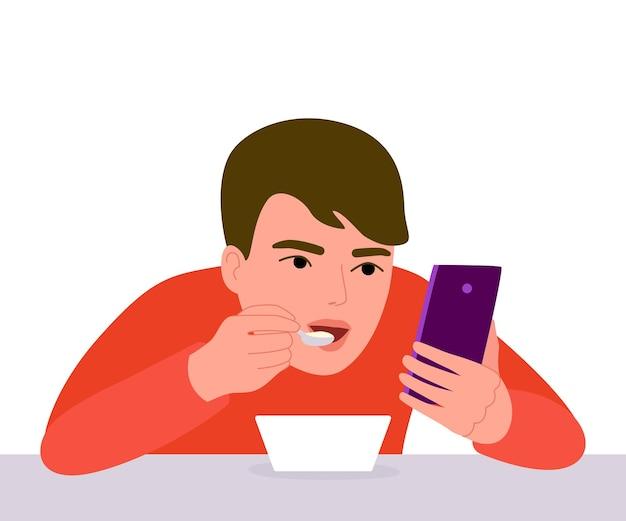 Menino come com o telefone nas mãos comendo e navegando no smartphone dependência de telefone