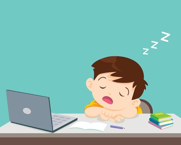 Menino criança entediado de estudar dorme na frente do laptop.