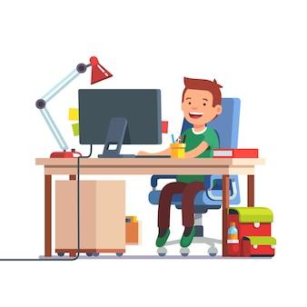 Menino da escola que estuda na frente do computador