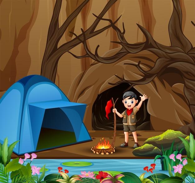 Menino de escoteiro no fundo de floresta de verão ao ar livre com tenda