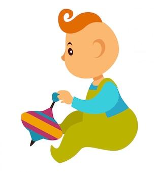Menino de macacão joga com whirligig brilhante