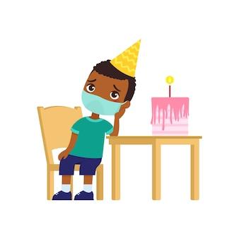 Menino de pele escura está triste no aniversário dela. garoto bonito com uma máscara médica no rosto se senta em uma cadeira. aniversário sozinho. proteção contra vírus, conceito de alergias.