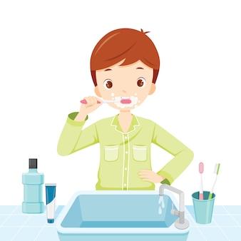 Menino de pijama escovando os dentes no banheiro