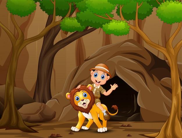 Menino de tratador feliz e leão na frente da caverna