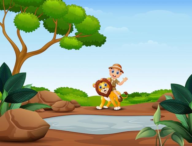 Menino de tratador feliz e leão perto da pequena lagoa