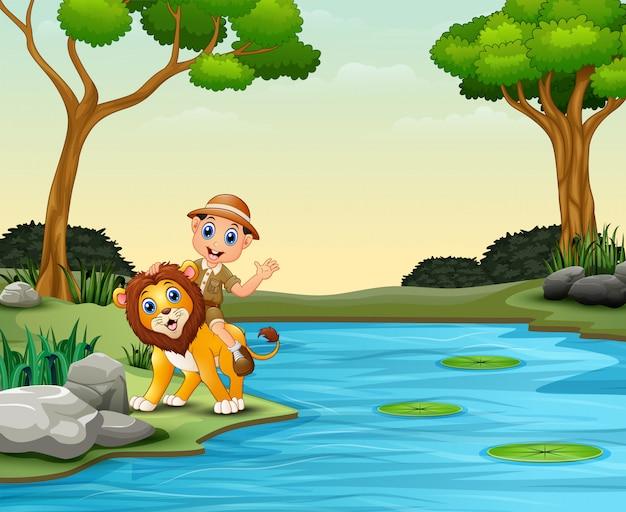 Menino de tratador feliz e leão perto de um rio