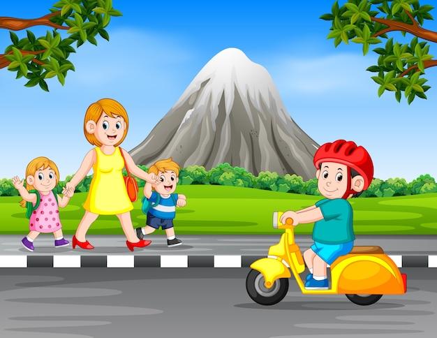 Menino dirigindo a motocicleta quando a mulher e seus filhos andam na estrada