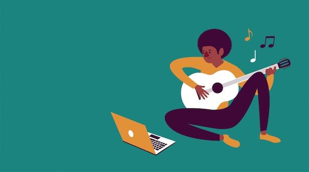 Menino e-learning para tocar violão com um laptop em casa