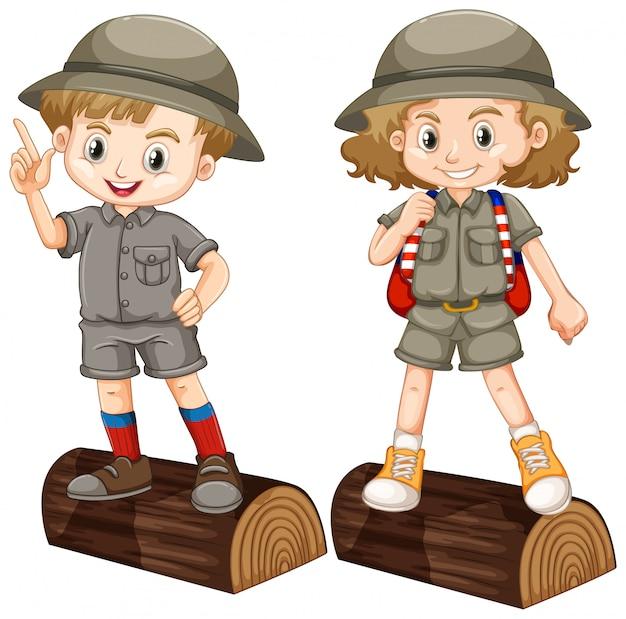 Menino e menina em traje de safari no log de madeira