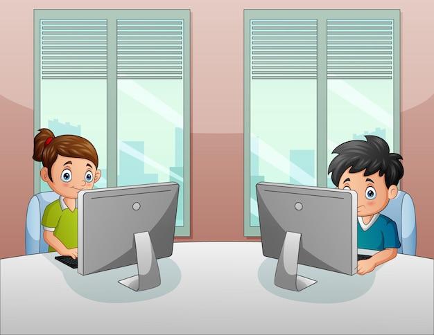 Menino e menina sentados na cadeira à mesa em frente ao computador