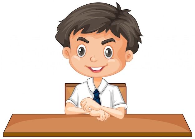 Menino em uniforme escolar, sentado na mesa em branco
