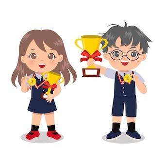 Menino esperto e menina com uniforme escolar posam com troféu e medalha de ouro.
