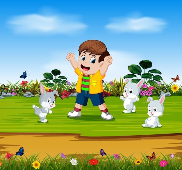 Menino está brincando com três coelhos no jardim