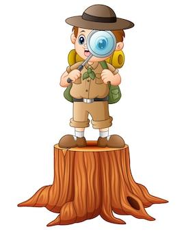 Menino explorador com lupa no toco de árvore