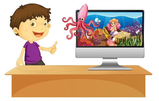 Menino feliz ao lado do computador com uma cena subaquática na tela