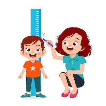Menino feliz criança fofa, medindo a altura com a mãe