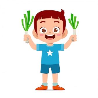 Menino feliz criança fofa segurando legumes frescos