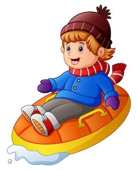 Menino feliz dos desenhos animados que monta um trenó inflável