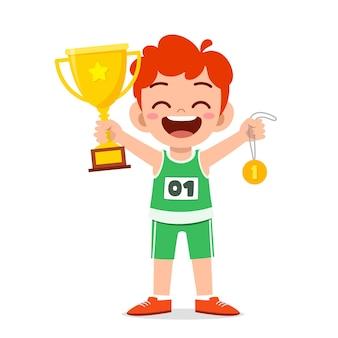 Menino feliz e fofo segurando uma medalha de ouro e um troféu