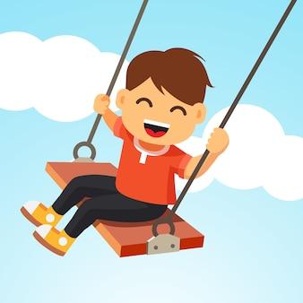 Menino feliz sorridente balançando em um balanço