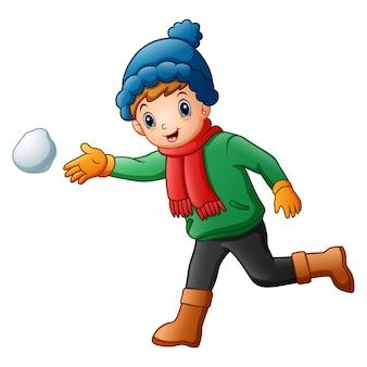 Menino fofo com roupas de inverno jogando bola de neve