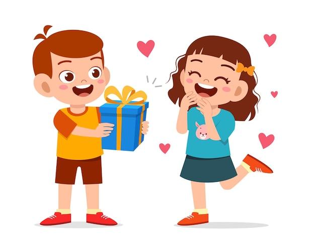 Menino fofo dar um presente para a menina para comemorar o aniversário