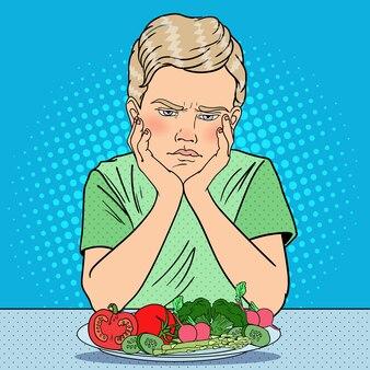 Menino infeliz com prato de legumes frescos