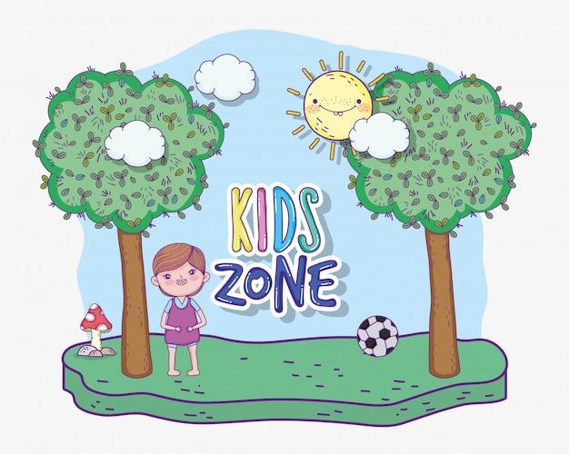 Menino joga futebol com bola e árvores