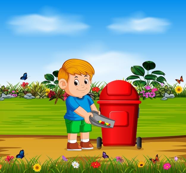 Menino jogar as coisas de perigo para a lixeira vermelha no jardim