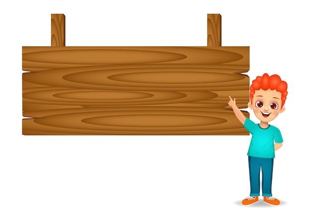 Menino mostrando o dedo indicador para uma placa de madeira em branco