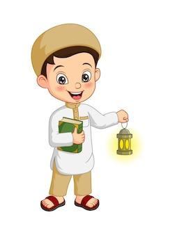 Menino muçulmano de desenho animado segurando o livro do alcorão com lanterna do ramadã