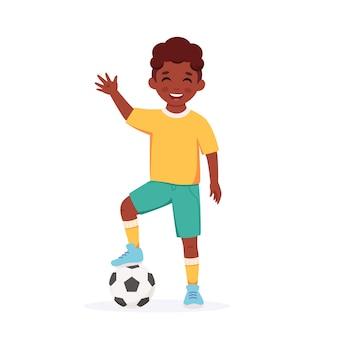Menino negro jogando futebol atividade infantil ao ar livre