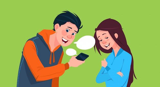 Menino novo e menina que falam guardando o conceito social do estilo de vida de uma comunicação dos meios do telefone esperto da pilha