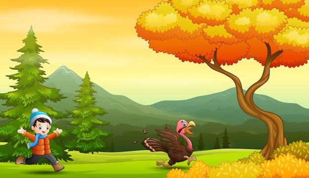 Menino perseguindo um peru no parque