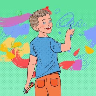 Menino pré-escolar de pop art desenhando na parede
