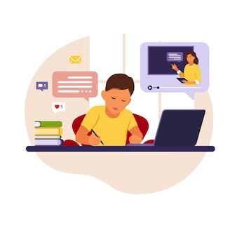Menino sentado atrás de sua mesa, estudando online usando seu computador. com mesa de trabalho, laptop, livros.