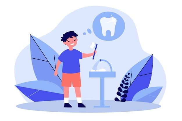 Menino sorridente a limpar os dentes pela saúde