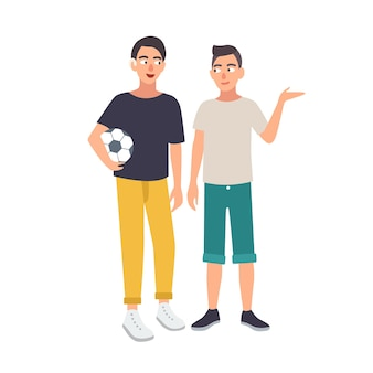 Menino sorridente com deficiência auditiva segurando uma bola de futebol e em pé com o amigo