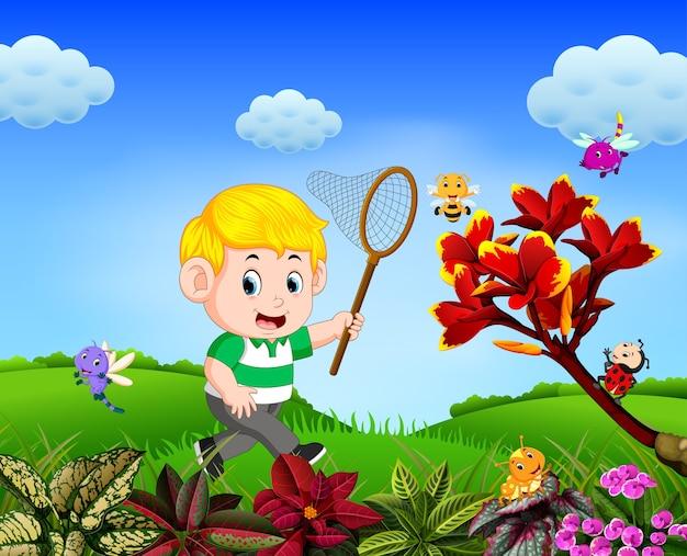 Menino tenta pegar uma borboleta no jardim