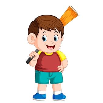 Menino, usando, a, vermelho, cloreis, segurando, a, vassoura, para, limpeza, a, lixo