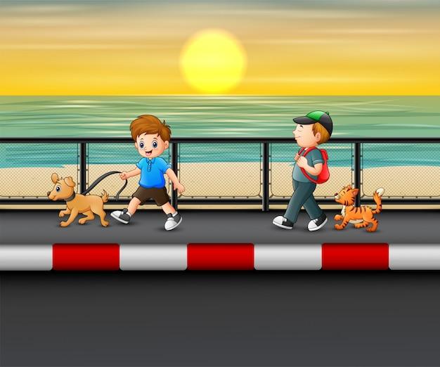 Meninos com seus cães andando perto da costa