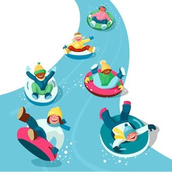 Meninos e meninas em roupas de inverno se divertem enquanto descem de trenó descendo a colina em tubos de neve.