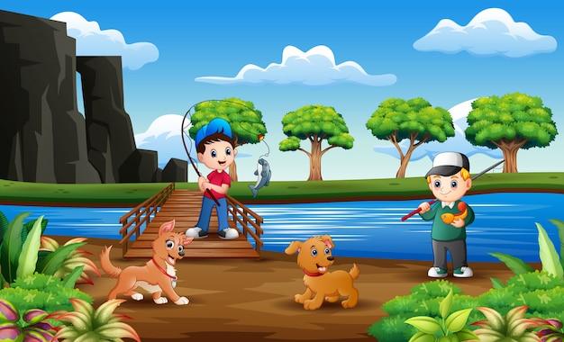 Meninos felizes que pescam com seu animal de estimação na ponte de madeira