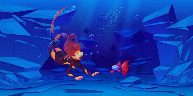 Mergulhador de mulher com máscara olha peixes bonitos debaixo d'água no mar ou oceano.